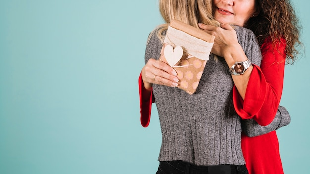 Crop mother hugging daughter for gift Free Photo