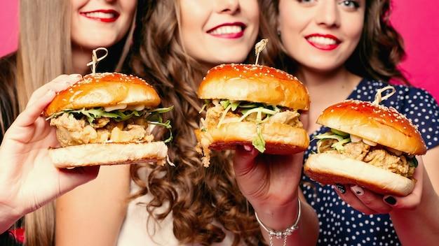 鶏肉と野菜のおいしいハンバーガーを保持している友人の作物。 Premium写真