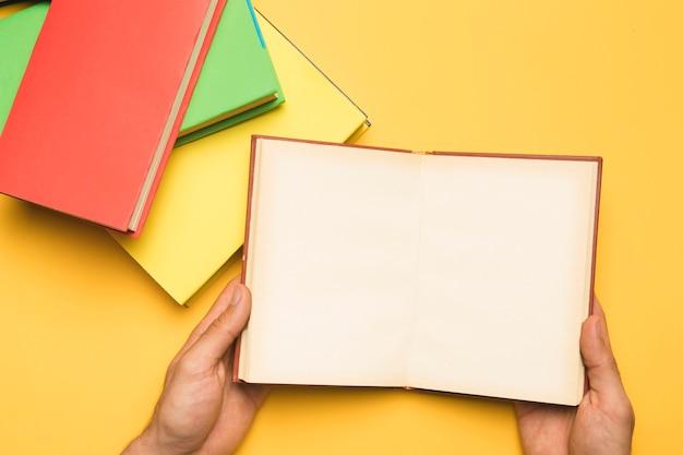書籍のスタックの近くに開いているノートブックを保持している人をトリミングします。 無料写真