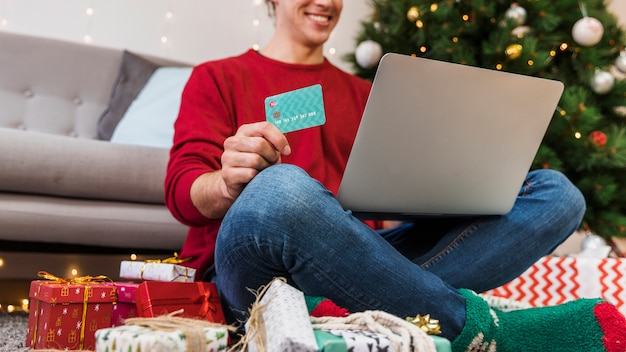 Crop person with card using laptop for shopping Free Photo