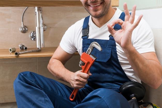Crop plumber gesturing ok Free Photo