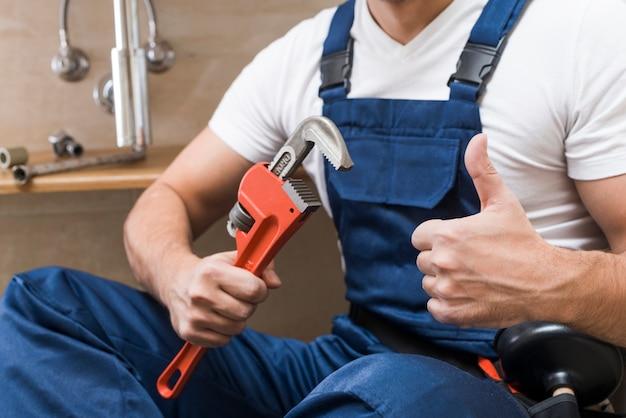 Crop plumber gesturing thumb up