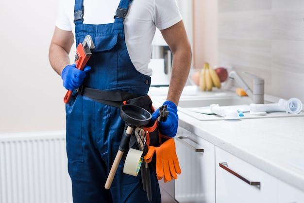 Crop plumber on kitchen Free Photo
