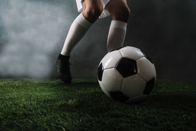 Crop soccer player shooting ball in smoke Free Photo