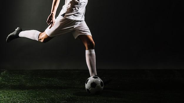 Кубок спортсмена, пинающий футбольный мяч Premium Фотографии