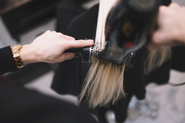 Crop stylist setting hair with brush Free Photo