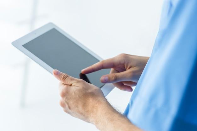 Crop surgeon browsing tablet Free Photo