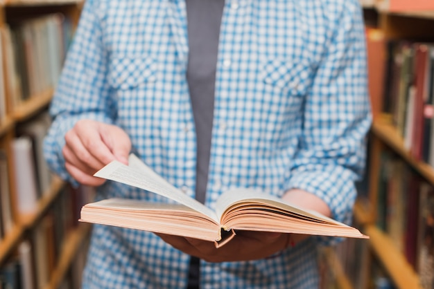 Crop teenager flipping pages of book Free Photo