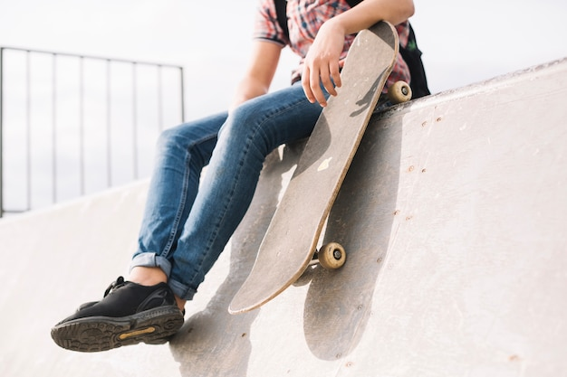 Crop teenager with skateboard sitting on ramp Free Photo