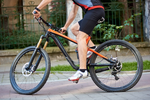 Crop view of male cyclist riding bicycle along paved streets Premium Photo