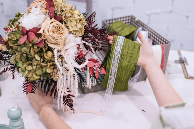 Crop woman decorating bouquet Free Photo