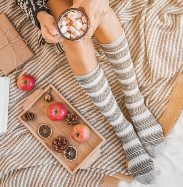 Crop woman drinking hot chocolate on bed Free Photo