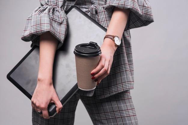 Crop женщина, держащая ноутбук и чашка Бесплатные Фотографии