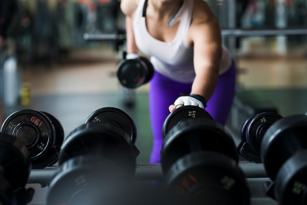 Crop woman lifting dumbbell in gym 23 2147789559