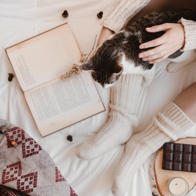 crop-woman-petting-cat-near-book-chocola