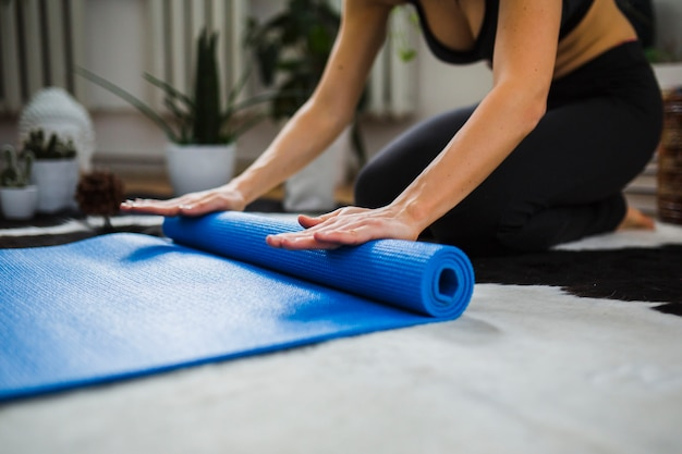 Crop woman rolling up yoga mat Free Photo
