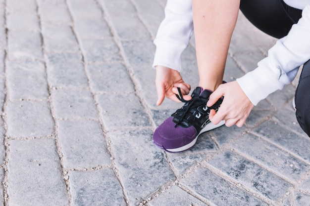 Crop woman tying laces on sneakers 23 2147800938