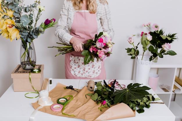 Урожай женщина, работающая с цветами и бумагой Бесплатные Фотографии