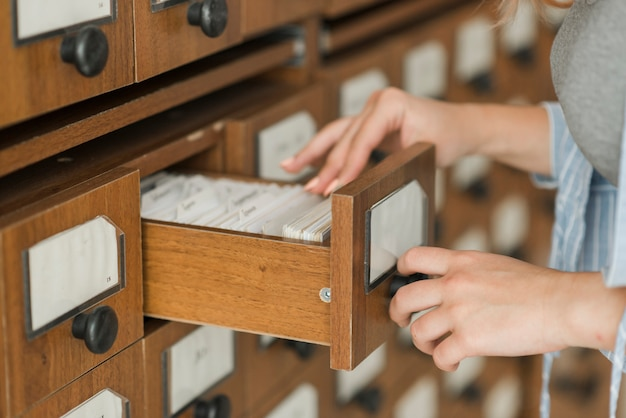 Raccogli la giovane donna che guarda dentro il cassetto delle biblioteche Foto Gratuite