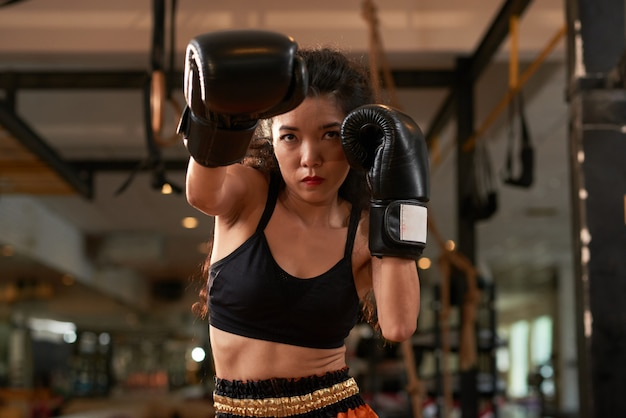 Cropped asian woman training in boxing gloves at muay thai practice Free Photo