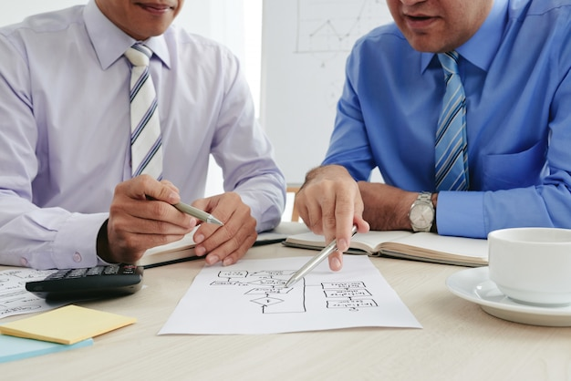 Cropped businessmen strategizing with a business chart Free Photo