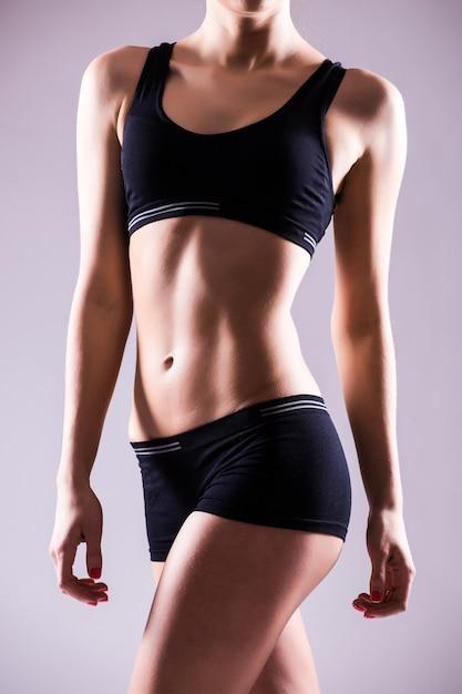 슬림 한 아름다운 복부와 복근을 보여주는 반바지와 스포츠 탑을 입고 맞는 여성의 몸을 자른 가까이 무료 사진