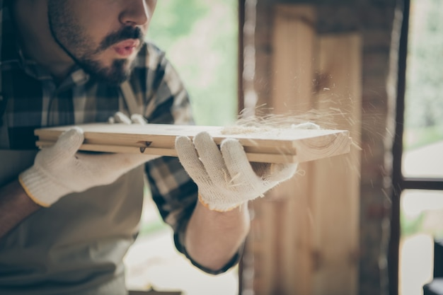 Cropped close up  serious confident man blowing sawdust away from wooden block before polishing Premium Photo