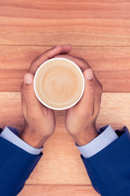 Cropped hand of businessman holding disposable coffee cup at wooden desk Premium Photo