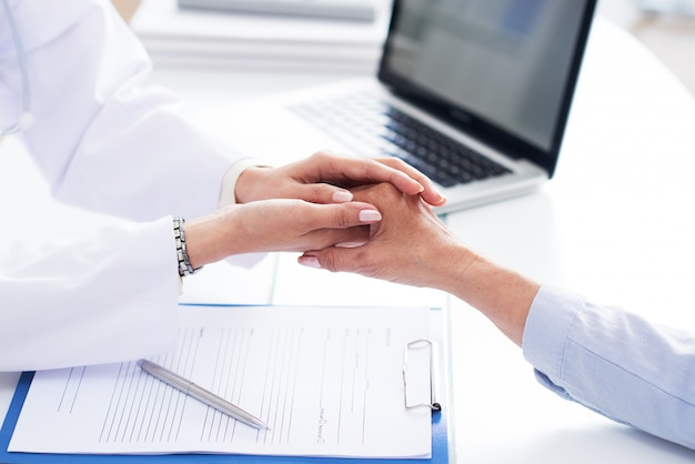 Cropped hands of doctor comforting unrecognizable patient Free Photo