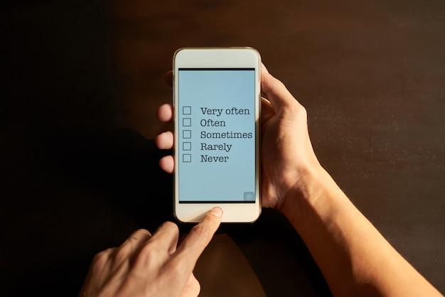 スマートフォンのタッチスクリーンでオンライン調査に記入する手をトリミング 無料写真