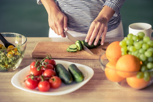 Cropped image of attractive girl cutting cucumber. Premium Photo