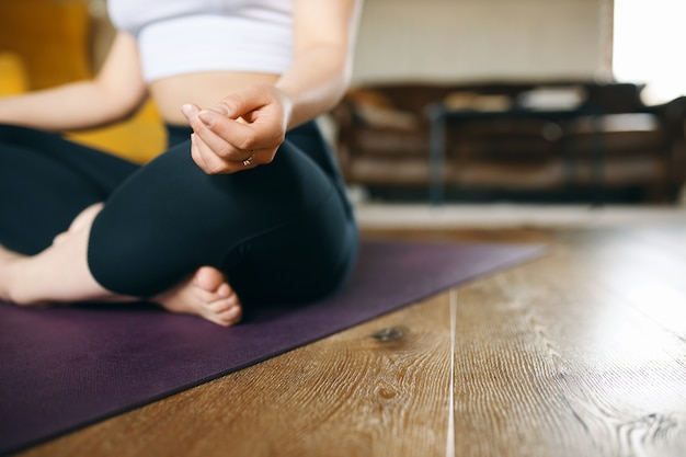 Cropped image of fit muscular young female in sports clothes meditating on floor in half lotus pose, making mudra gesture, sitting on mat before yoga practice, concentrating on feelings and breathing Free Photo