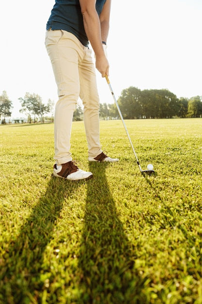 Cropped image of a golfer putting golf ball on green Free Photo