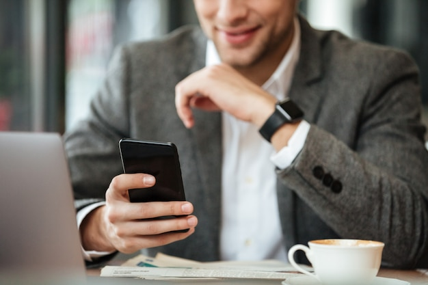 Cropped image of happy businessman sitting by the table in cafe and using smartphone Free Photo