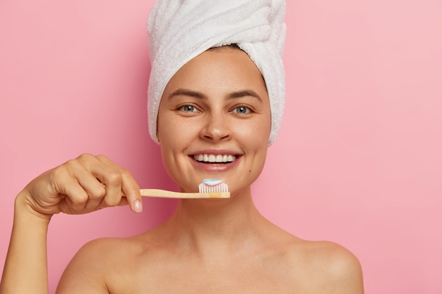 Immagine ritagliata della donna europea felice si lava i denti, tiene lo spazzolino da denti con dentifricio, indossa un asciugamano avvolto sulla testa, ha una pelle sana e fresca, sta nudo Foto Gratuite