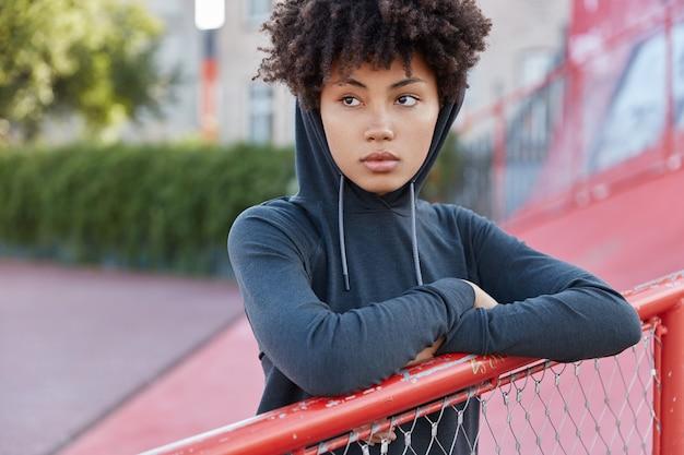 魅力的な暗い肌の女の子のトリミングされた画像は、スタイリッシュなパーカーを着て、ぼやけた背景に対して屋外に立っています 無料写真