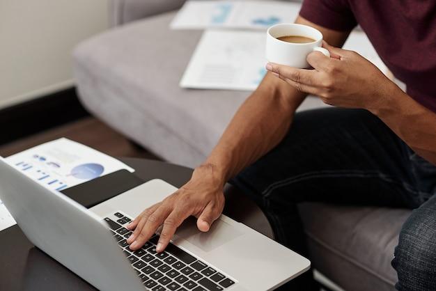 クライアントからの電子メールに応答するときに一杯のコーヒーを飲む起業家のトリミングされた画像 Premium写真