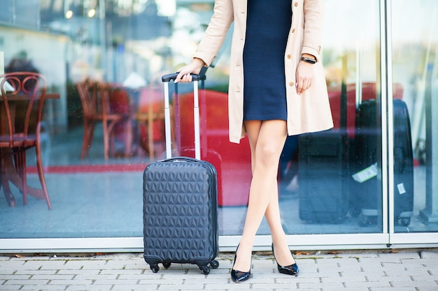 Cropped image traveler tourist woman crossed legs in summer casual clothes with suitcase on road in city outdoor. girl traveling abroad to travel on weekends getaway. tourism journey lifestyle Premium Photo