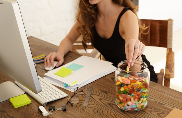 Cropped image of young stressed woman eating sweets at workplace in office. the girl takes candy from big glass jar with lollipops standing on a desktop. stress and junk food concept Free Photo