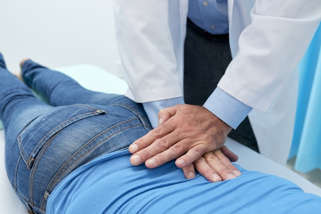 Cropped osteopath adjusting back of patient with massage Free Photo
