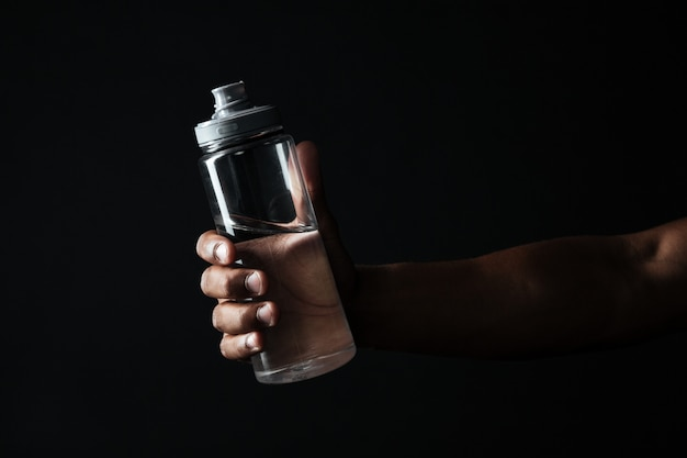 Cropped photo of afro american males hand holding bottle with water Free Photo
