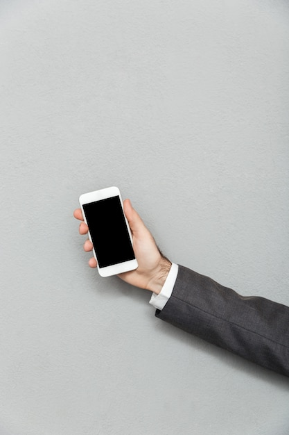 Cropped photo of male hand holding smartphone with blank screen isolated over gray, copy space Free Photo