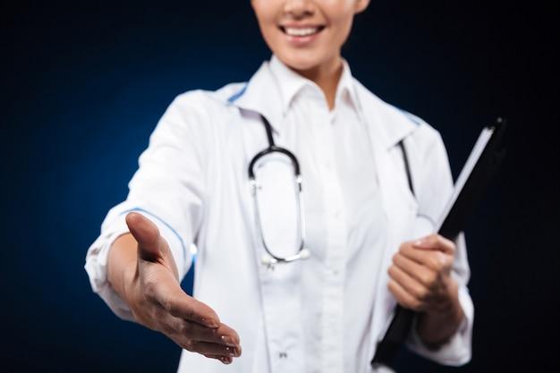 クリップボードを保持している陽気な看護師の写真をトリミングし、手を差し伸べる 無料写真