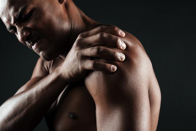 肩の痛みを持つ上半身裸のアフロアメリカンの若者の写真をトリミング 無料写真