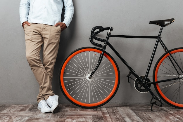 Cropped picture of african man standing near bicycle Free Photo