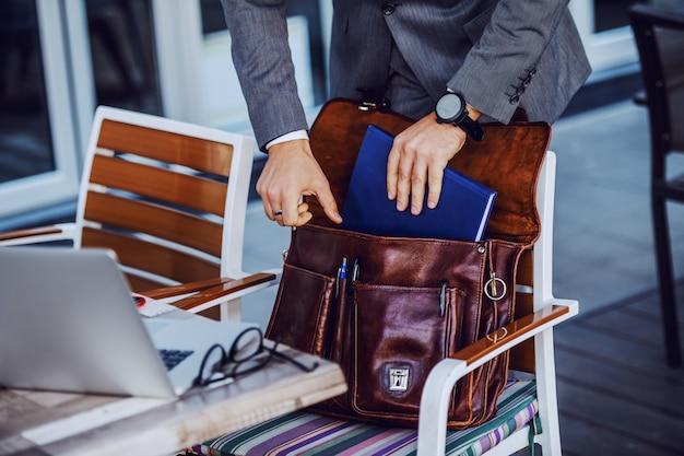 彼の革のバッグから議題を取り出すスーツを着たエレガントなビジネスマンの写真をトリミングしました。カフェ外観。 Premium写真