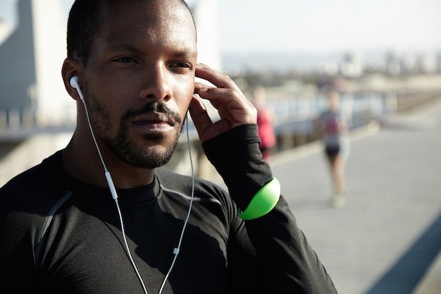 Cropped portrait of black sportsman sitting on pavement in deep thoughts, listening to motivative audiobook in his headphones, touching his head, looking confident and concentrated during workout Free Photo