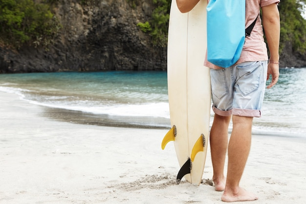 Обрезанный портрет босого молодого серфера, стоящего на песчаном пляже на фоне высокого скалистого берега с растительностью, несущего белую доску для серфинга, готового ударить по волнам Бесплатные Фотографии
