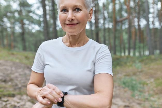 그녀의 손목에 스마트 시계를 조정하는 흰색 티셔츠에 아름다운 중년 여성의 자른 초상화 무료 사진