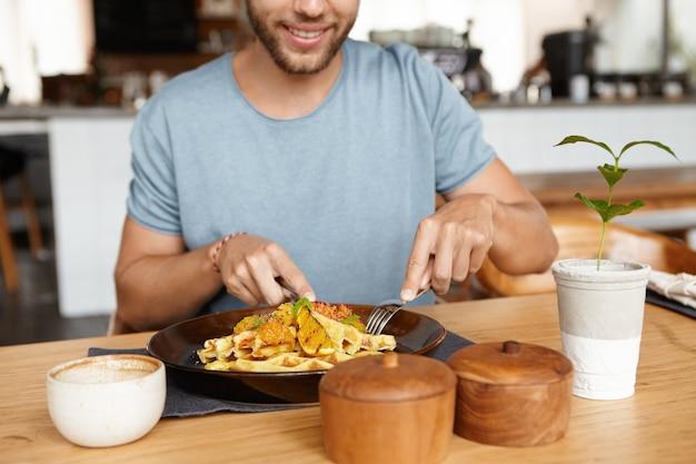 Обрезанный портрет счастливого молодого бородатого мужчины в футболке, весело улыбаясь, наслаждаясь вкусной едой во время обеда в уютном ресторане, сидя за деревянным столом Бесплатные Фотографии